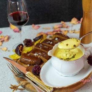 Easy to Make Exquisite Vegan Béarnaise Sauce accompanied by our vegan steak cut into thick slices and red wine