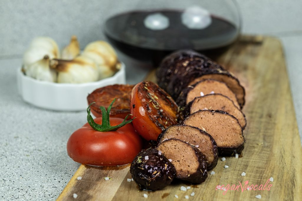 Filetes de Lomo de Seitan (Filet Mignon Vegano) cortado en rodajas, acompañado de tomates y vino tinto