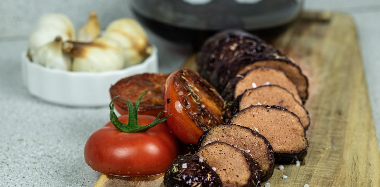 Photo showing Succulent Vegan Filet Mignon (Wheat Meat) cut into pieces accompanied by grilled tomato and red wine