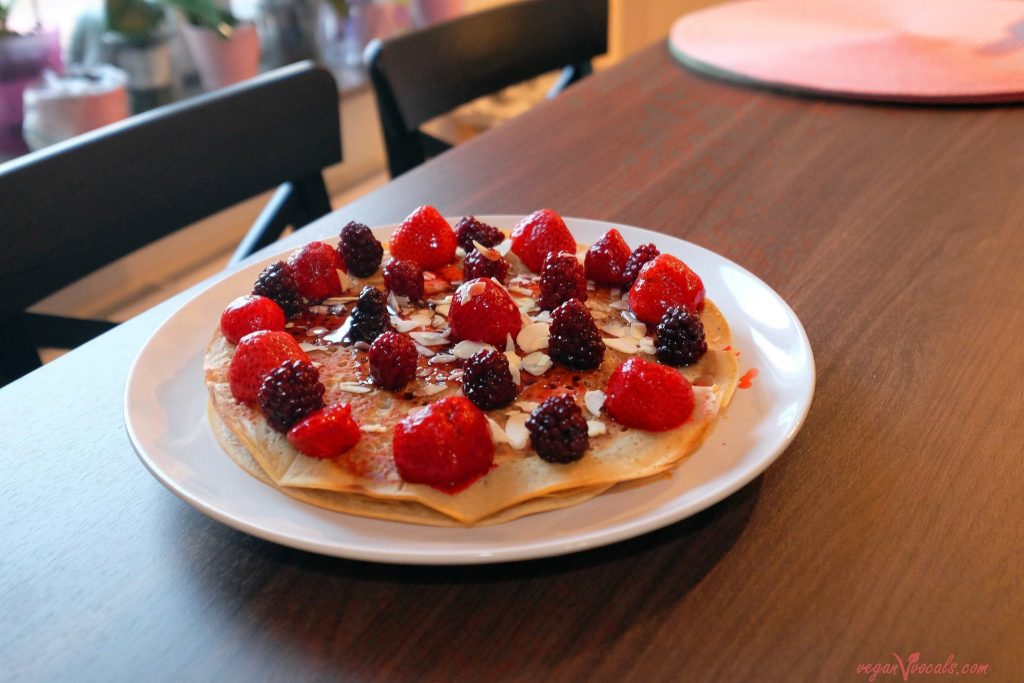 Vegan oil-free pancakes with berries, sliced almonds and blueberry syrup